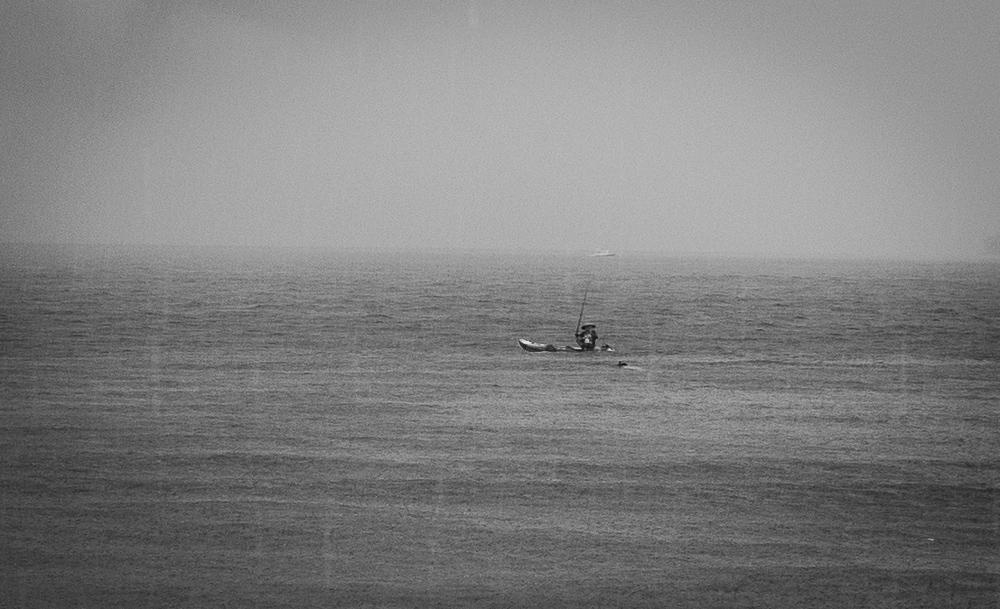 Diena, kai kokias 5h pylė lietus. Žvejas valtelėje į snorkeliuotoją žiūrį, kaip į iš dangaus nukritusį.